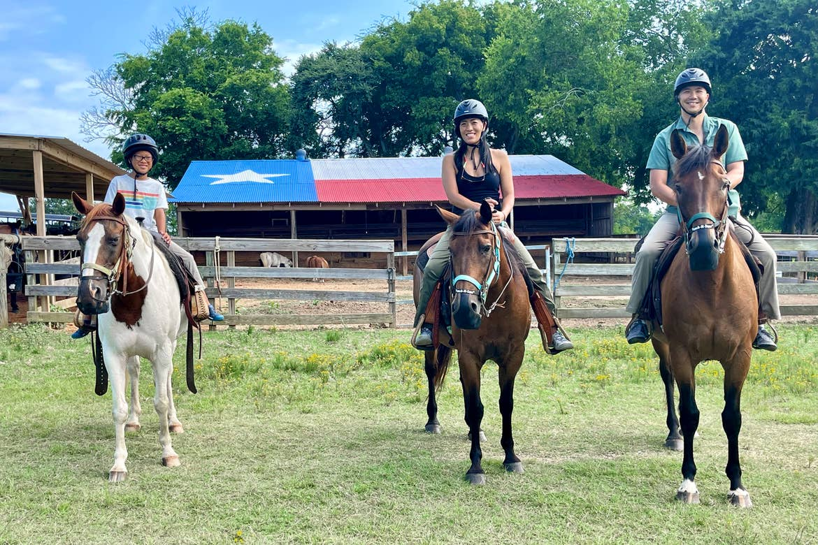 A young Asian boy (left), an Asian woman (middle) and Man (right) wear safety helmets while riding horseback near a building with a galvanized roof with the Texas flag painted on it.