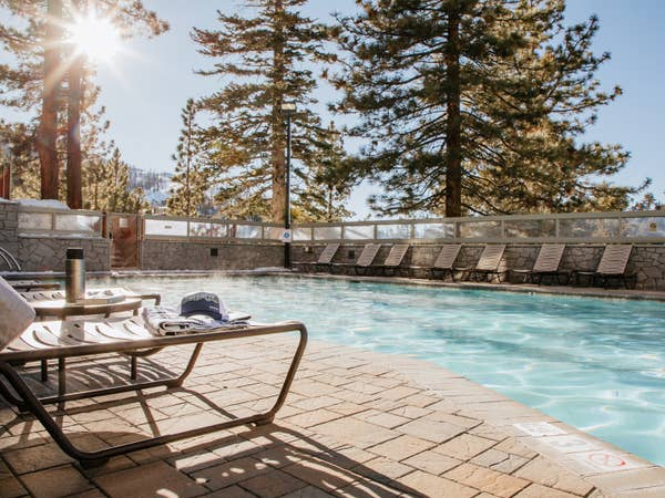 Outdoor pool surrounded by trees and pool chairs at Tahoe Ridge Resort in Stateline, Nevada.
