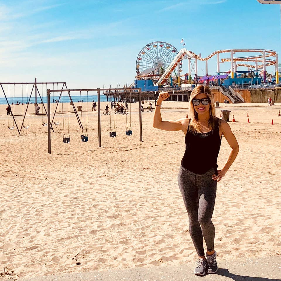 Featured Co-author, Christine, stands on Venice Beach wearing black tanks and leggings in front of the boardwalk and various exercise areas.