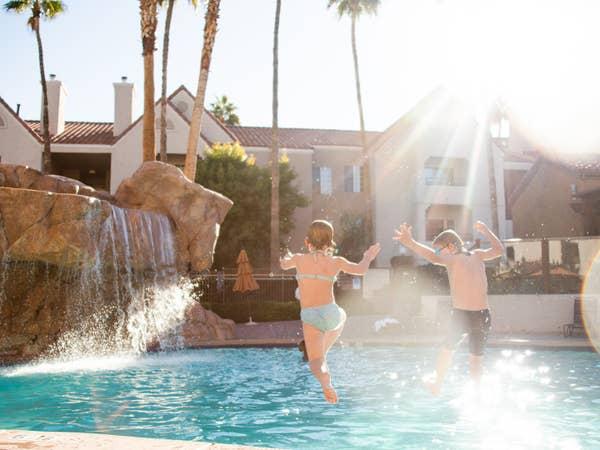 Two kids jumping into outdoor pool at Desert Club Resort in Las Vegas, Nevada.