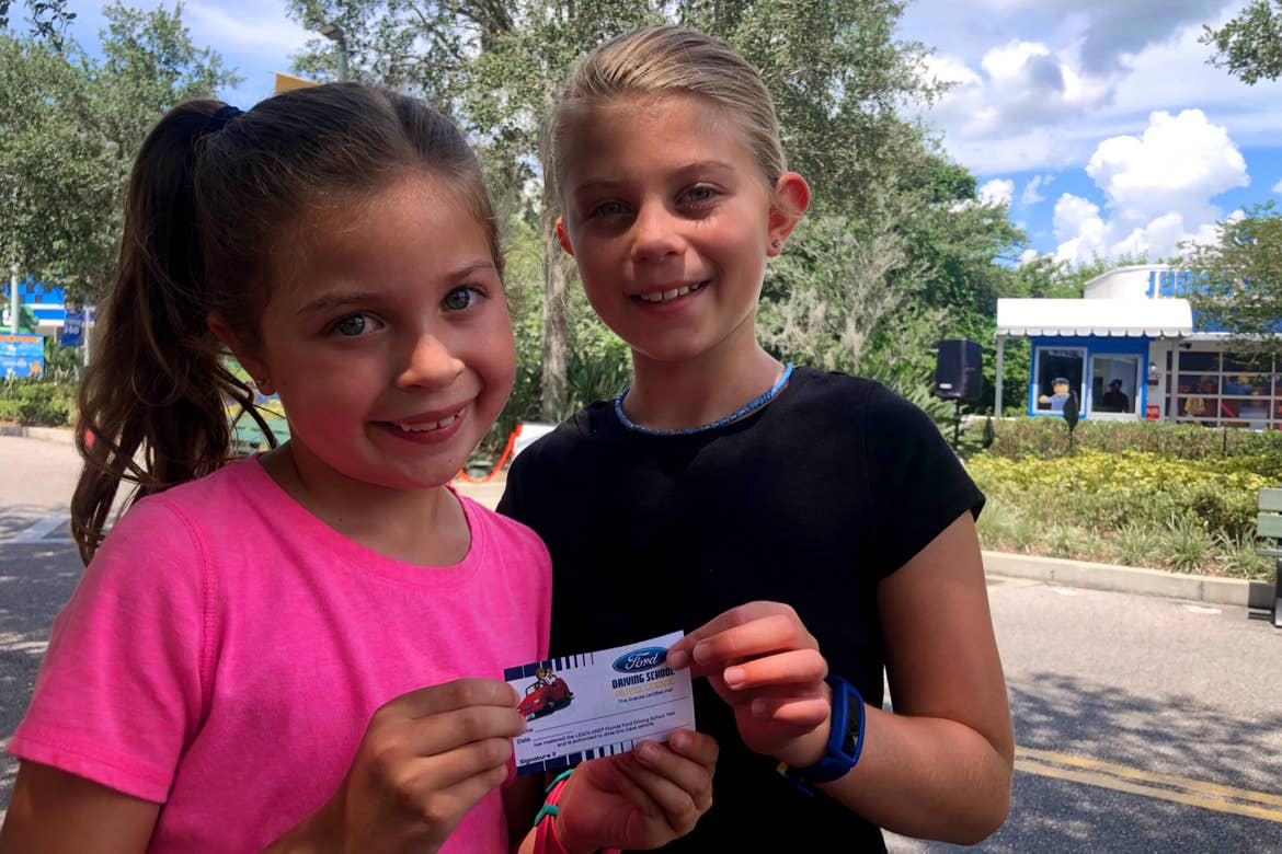 Two young girls stand holding an Unofficial LEGO Drivers License.