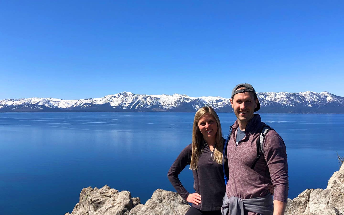 A woman (left) black pullover while hugging a man (right) wearing a red pullover and grey hat in front of a mountain range at Lake Tahoe, Nevada.