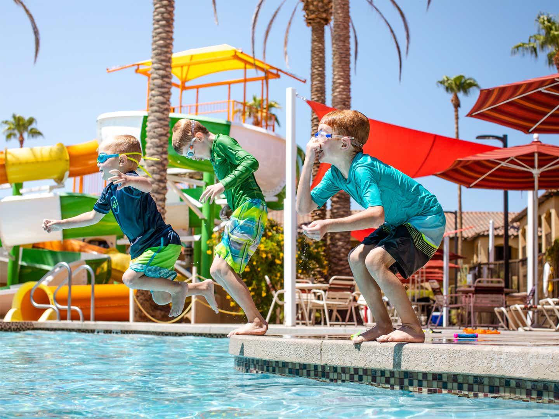 Three children jumping in pool