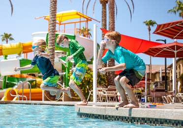 Three children jumping in pool in Splash Canyon water feature at Scottsdale Resort.