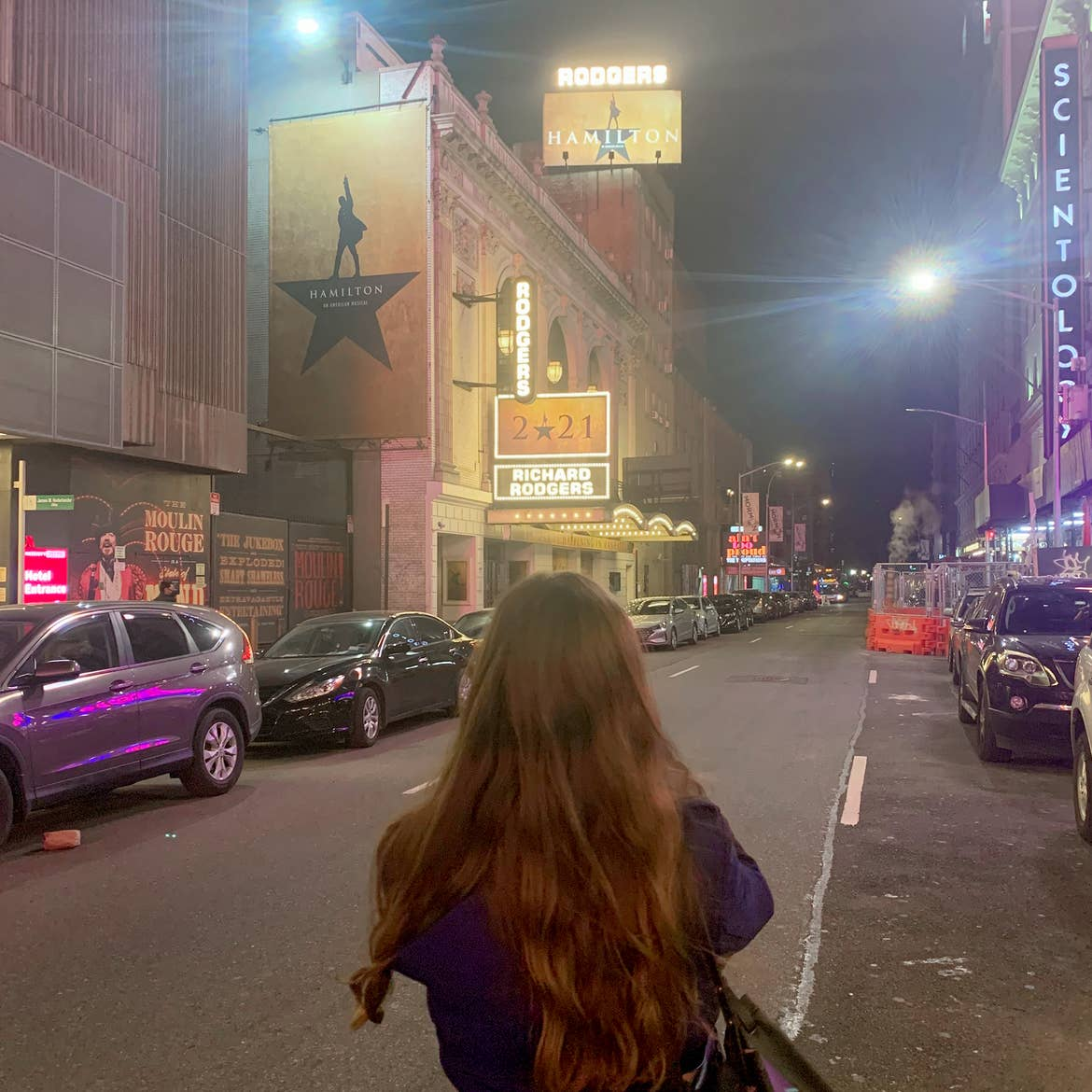 A caucasian woman with long ash-blonde hair wears a jacket under a marquee for the production of 'Hamilton' that reads, '2021' in New York City.