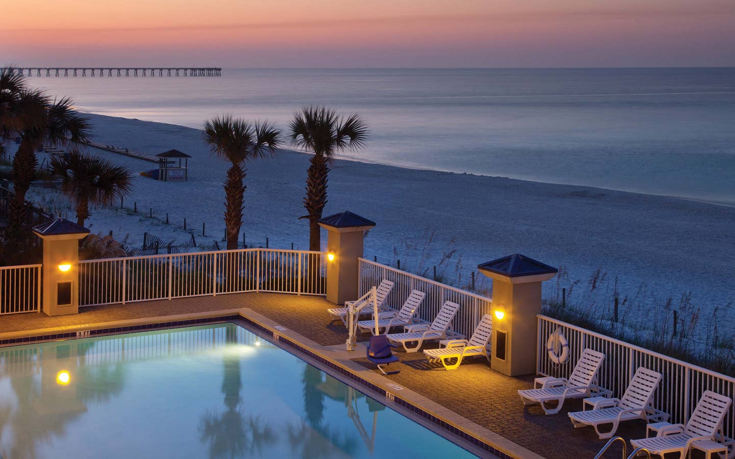 View of outdoor pool looking onto beach at sunset at Panama City Beach Resort in Florida.