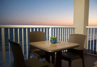 Furnished balcony with table and three chairs in a villa at Panama City Beach Resort