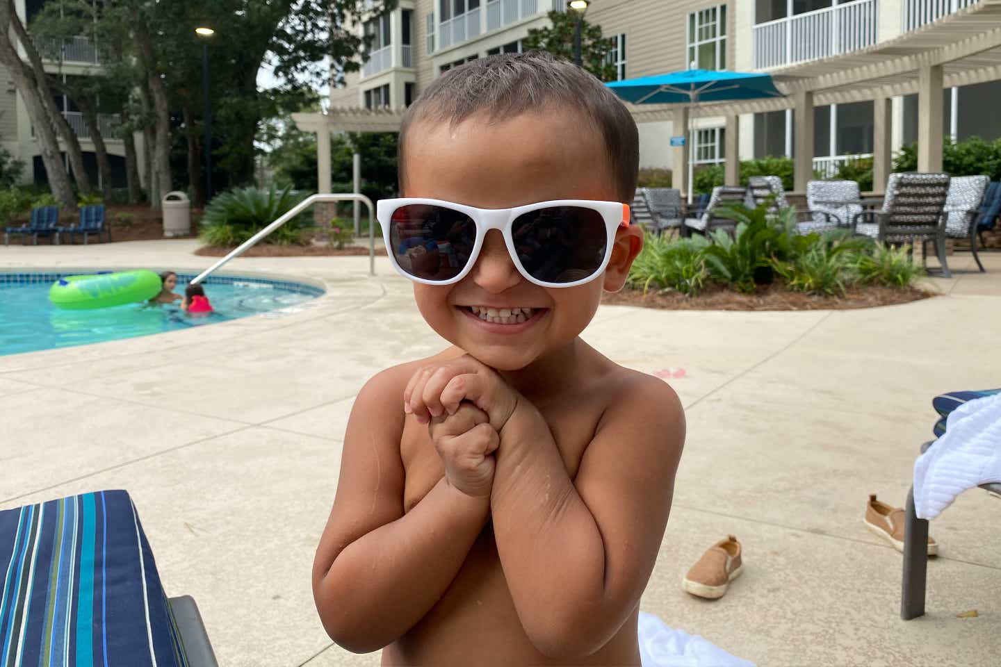 Brenda's son, Benjamin, wears white sunglasses next to mommy at the pool.