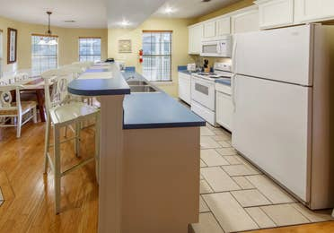 Kitchen with fridge, oven, microwave, dishwasher, and sink in a presidential two bedroom villa at Piney Shores Resort in Conroe, Texas