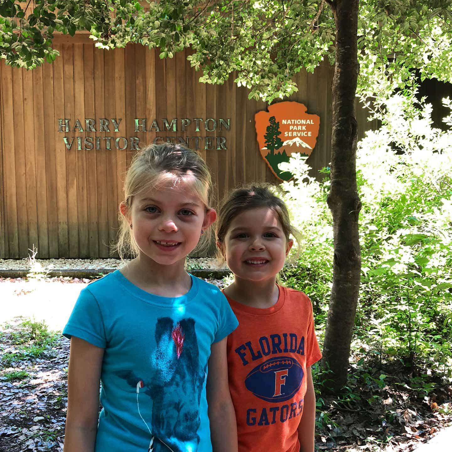 Author, Chris Johnstons' daughters, Kyndall (left), and Kyler (right) pose with a sign that reads, 'Harry Hampton Visitor Center, National Park Service.'