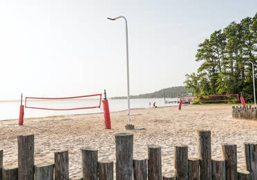 Two sand volleyball courts with view of lake at Villages Resort in Flint, Texas.