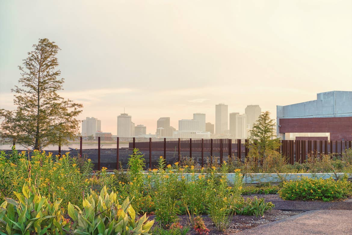 A view of the New Orleans skyline in the distance under a cloudy, sunset sky with brown iron fences and greenery at Crescent Park.