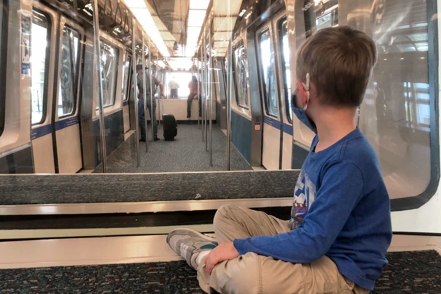 Sarah's son, Logan, sits on the bench of Orlando Airports terminal monorail.