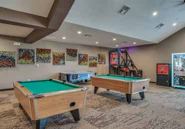 Game room with two pool tables, a pop-a-shot machine, claw machine, and air hockey table at Piney Shores Resort in Conroe, Texas