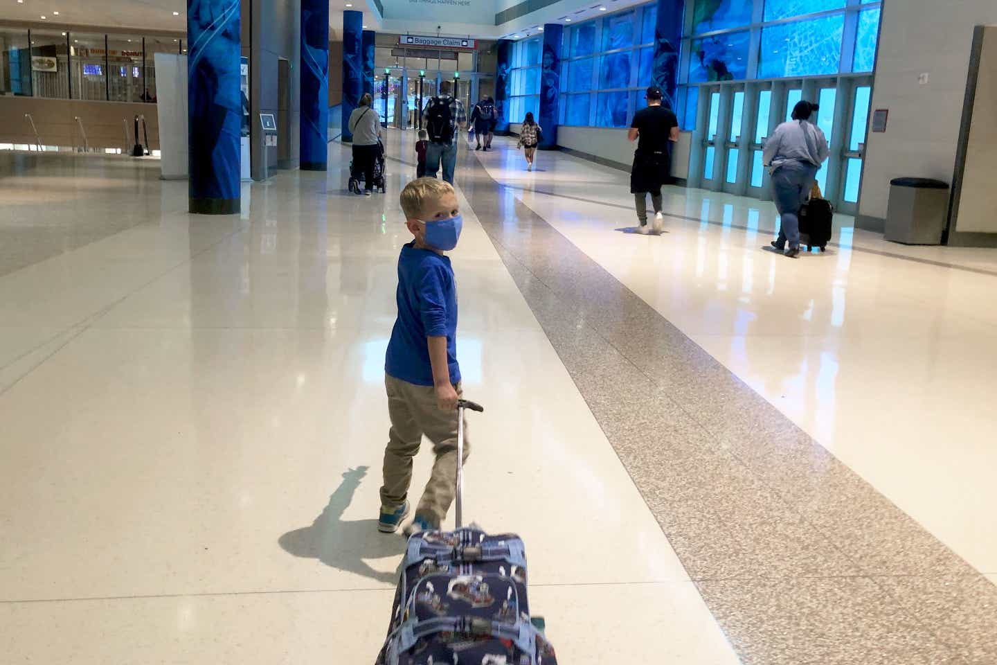 Sarah's son, Logan, pulls his suitcase wearing a mask they walk through the terminal.