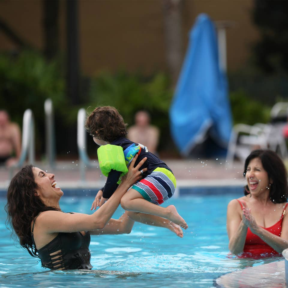 Mother playing with child in outdoor pool.