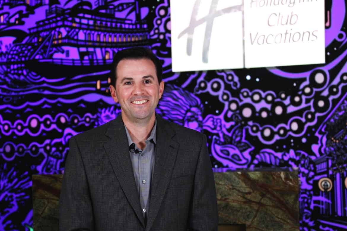 General Manager, Mike Larose, wears a black suit while standing in front of our animated mural projection in the lobby of our New Orleans resort in Louisiana.