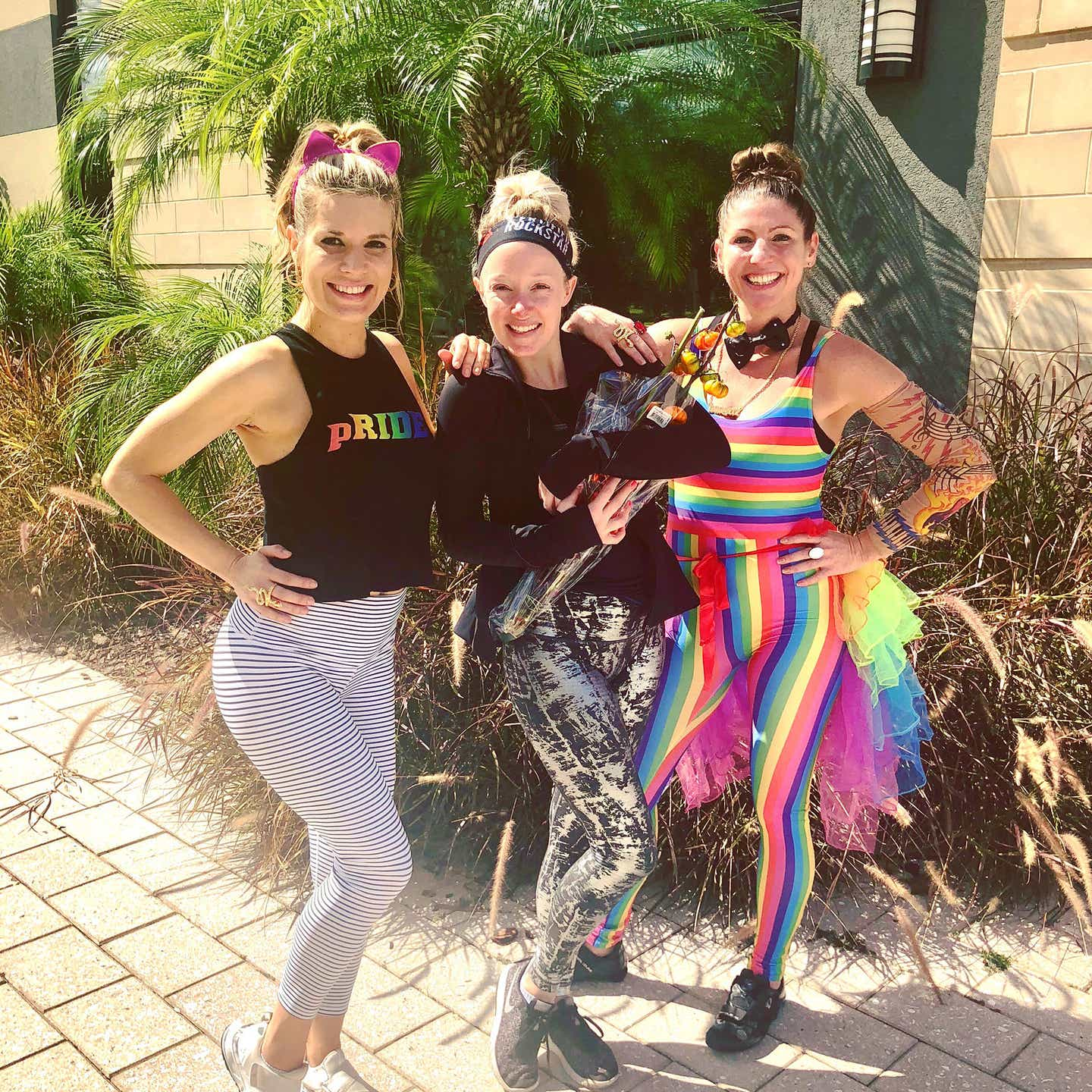 From left to right: Co-authors, Jessica, Molly and Christine wear PRIDE-inspired outfits together outdoors.