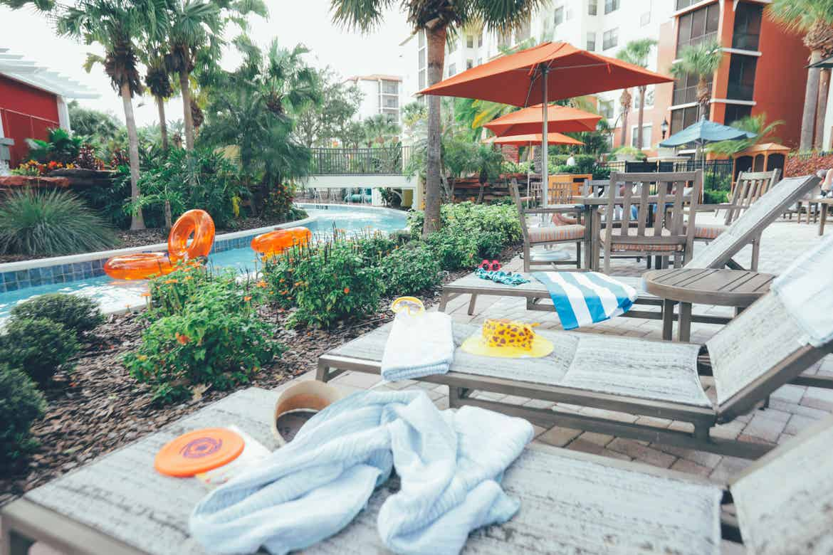 Beach chairs with swimming toys and towels placed next to our lazy river at Orange Lake Resort in Florida.