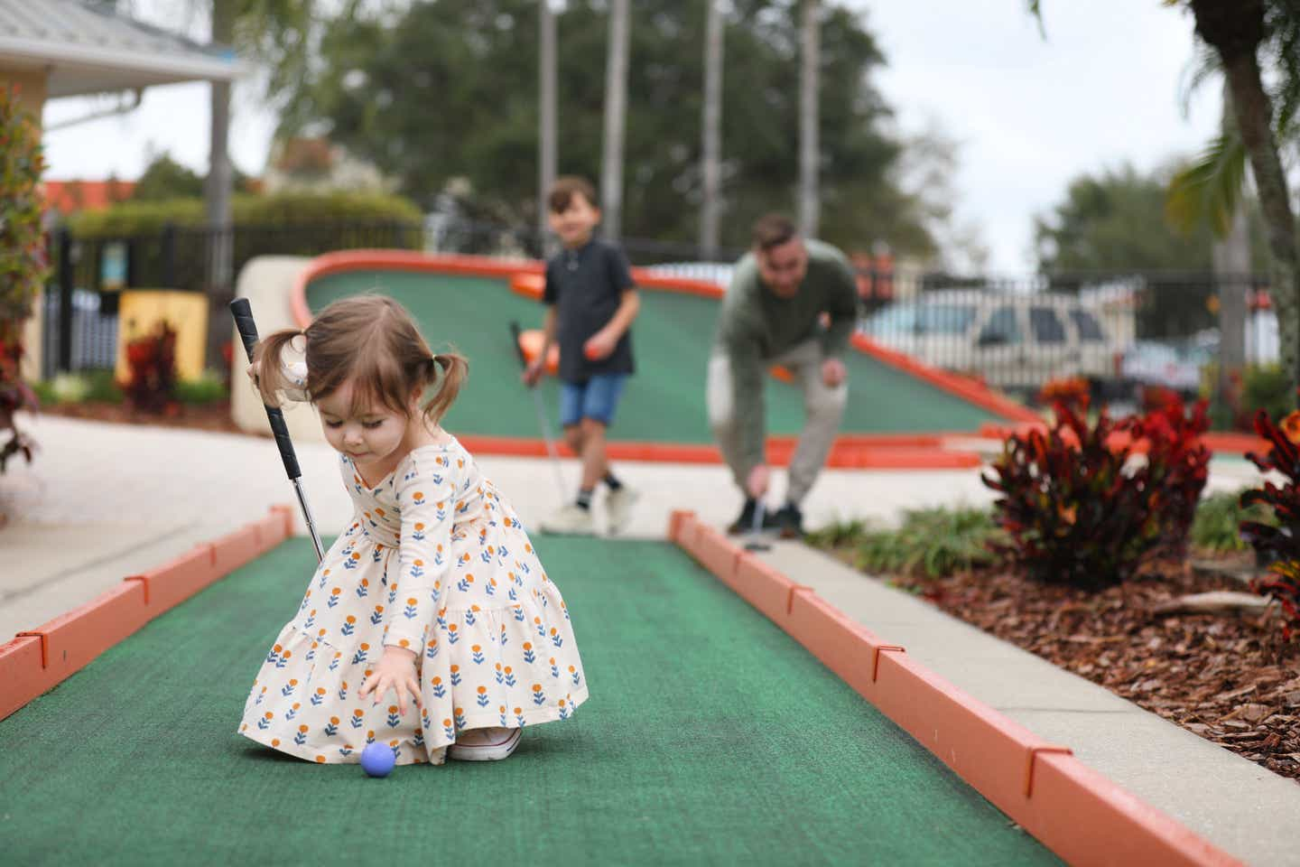 Mia St Clair's daughter picking up a blue golf ball at the mini golf course