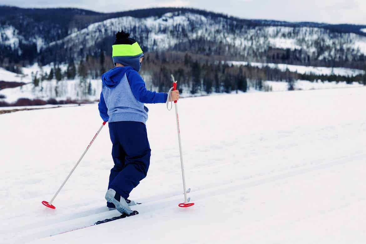 A boy wears cross country ski gear and a multicolor knit hat and blue-grey hoodie in white snow.