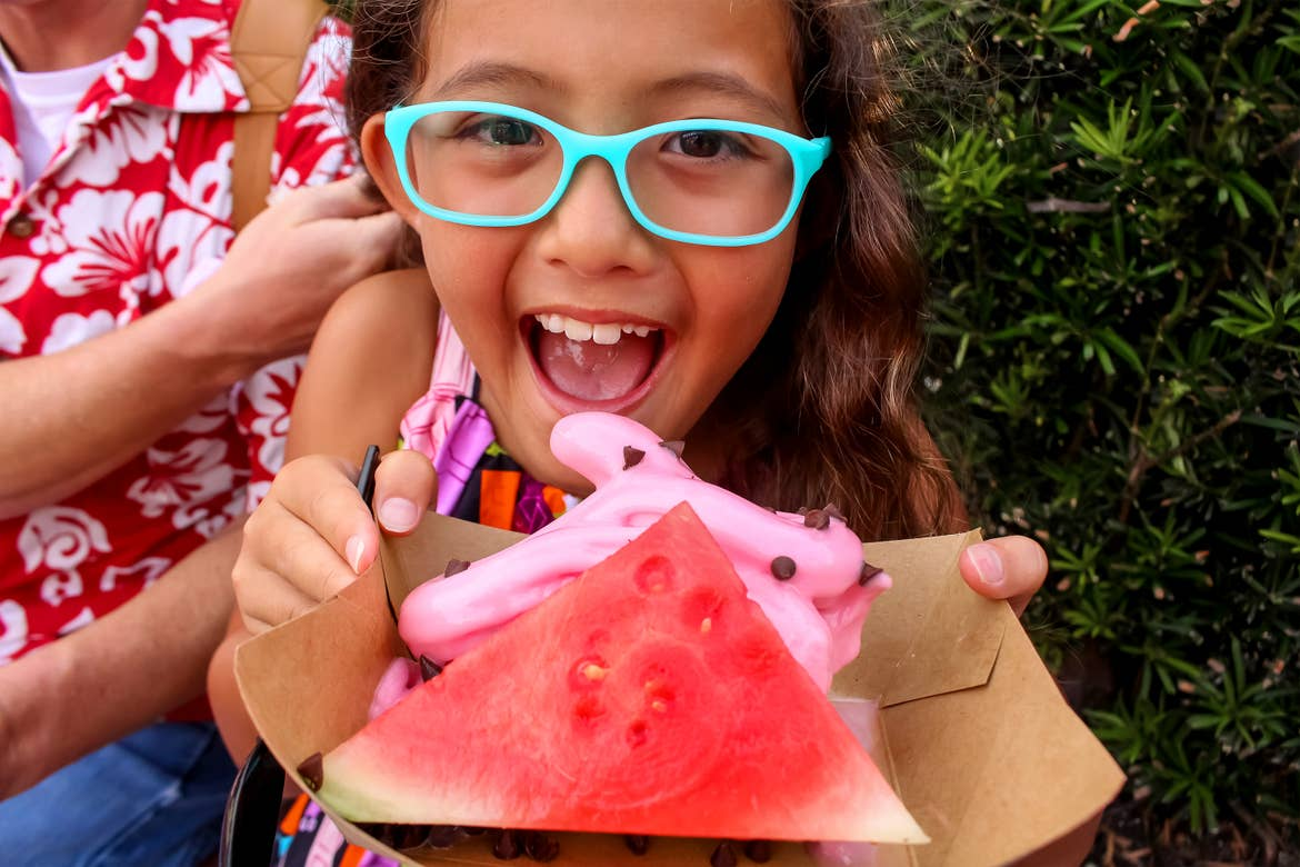An Asian girl wearing a multi-colored blouse and blue glasses holds a paper container with a slice of watermelon and pink, sot-serve ice cream with mini chocolate chips outdoors.