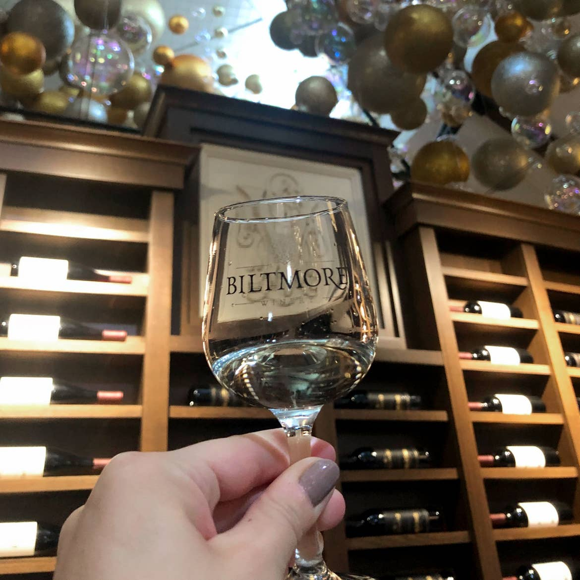 Author, Jennifer C. Harmon, holds a wineglass that reads, 'BILTMORE' in front of a wine shelf, with the ceiling decorated with festive silver, gold and white ornaments.