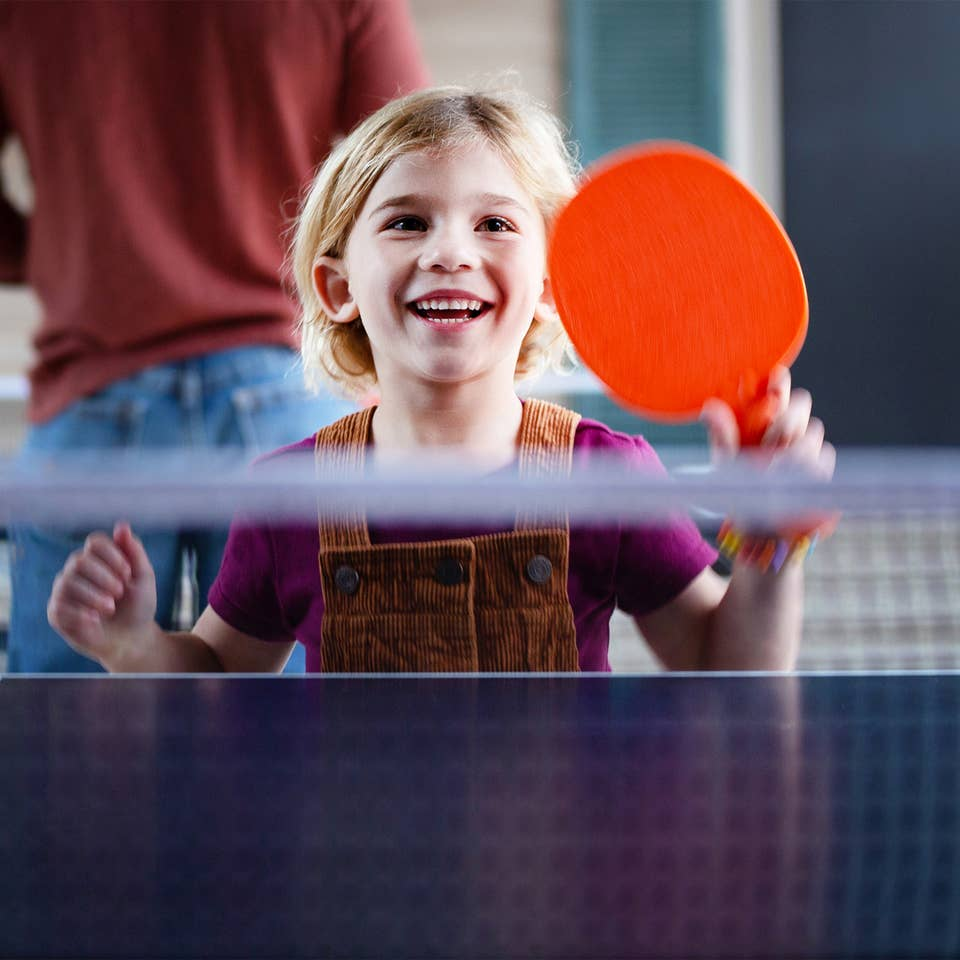 A young girl holding a paddle at a ping pong table