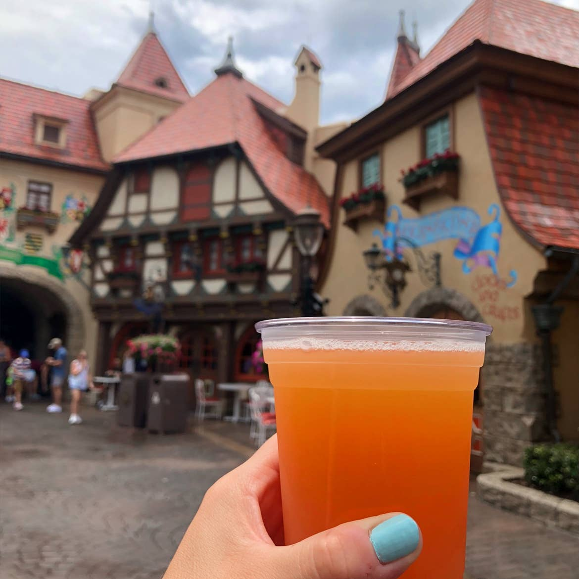 A hand holds a plastic cup of beer near the Germany Pavilion at Epcot in the rain.