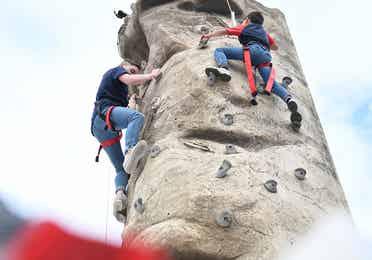 Two guests climbing on outdoor rock wall at Orange Lake Resort near Orlando, Florida.