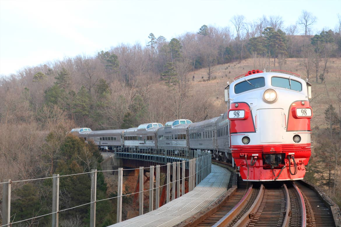 A Zephyr Scenic train in red approaches the foreground on it's tracks.