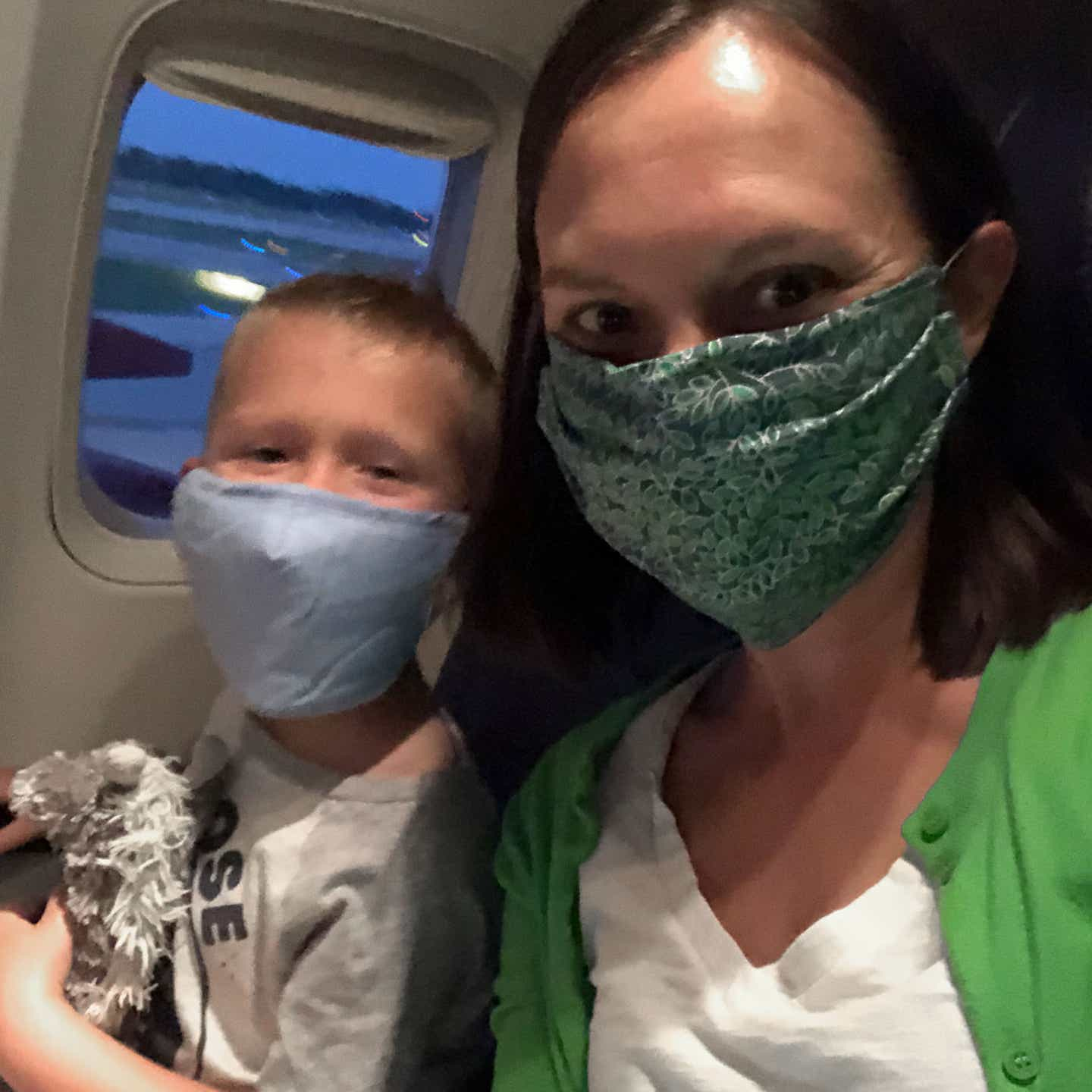 Author, Sarah, and son, Logan, sit near the window seat on their airplane wearing masks for safety.