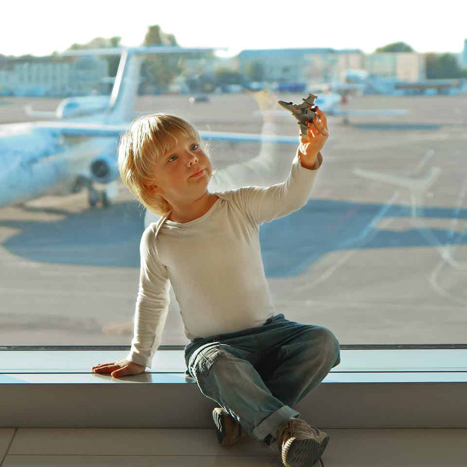 A young boy wearing a white long sleeve shirt plays with a toy airplane in front of an airport window near the runway with a white airplane.