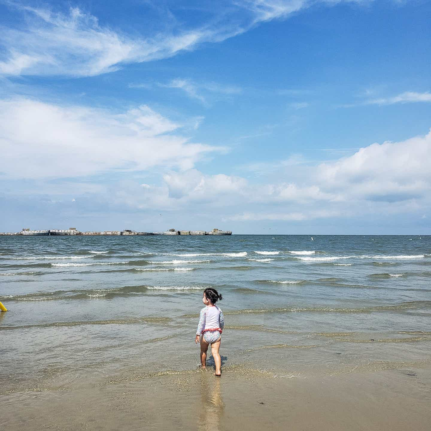 Angelica's daughter walking on the beach toward the waves, looking at the concrete fleet.