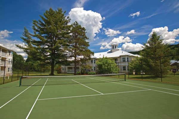 Tennis court surrounded by large trees at Oak n' Spruce Resort in South Lee, Massachusetts