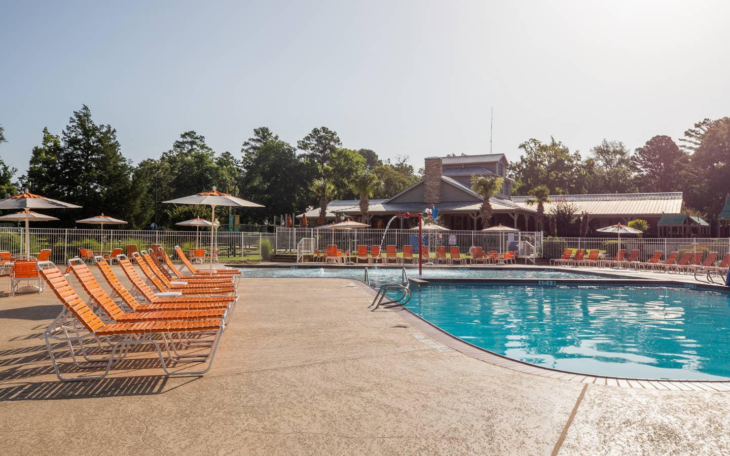 Outdoor pool with orange pool chairs surrounding it at Villages Resort in Flint, Texas.