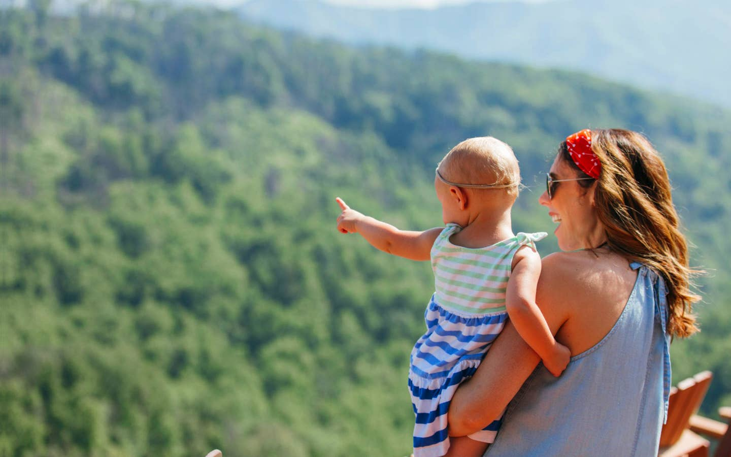A mother hods her daughter while overlooking the Great Smoky Mountains.