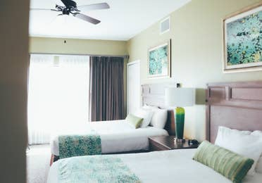 Two beds in a bedroom with large window in a villa in River Island at Orange Lake Resort near Orlando, Florida