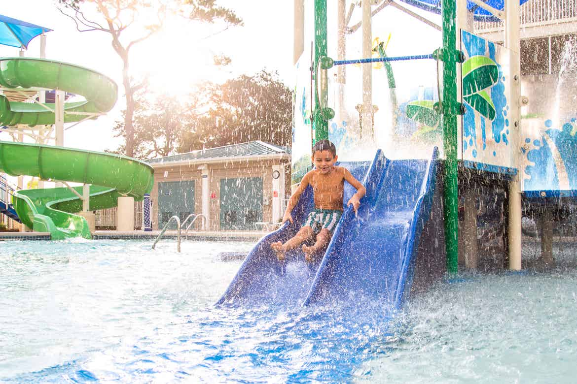 Author, Brenda Rivera Stearns' son slides down a blue slide into the pool at Splash Cove at our South Beach resort in Myrtle Beach, South Carolina.