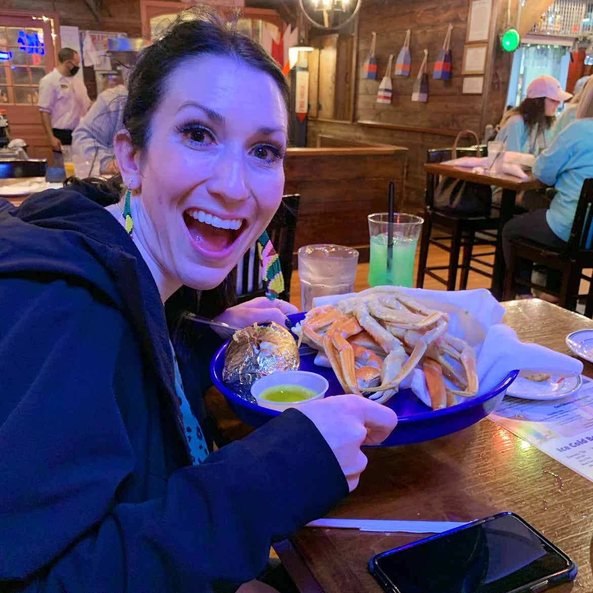 Featured Contributor, Amanda Nall's friend holds her Crab's Legs ordered at Fish Tales.