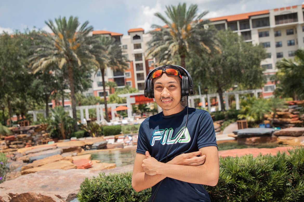 Special Olympic Athlete, Roan Luallen, smiles as he wears a black shirt and a headset in front of the lazy river at our Orange Lake Resort located in Orlando, Florida.