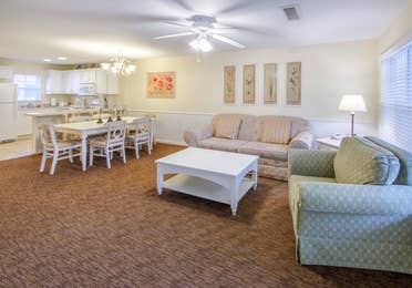 Large living area with sitting area, dining room and kitchen in a two bedroom presidential villa at Oak n' Spruce Resort in South Lee, Massachusetts
