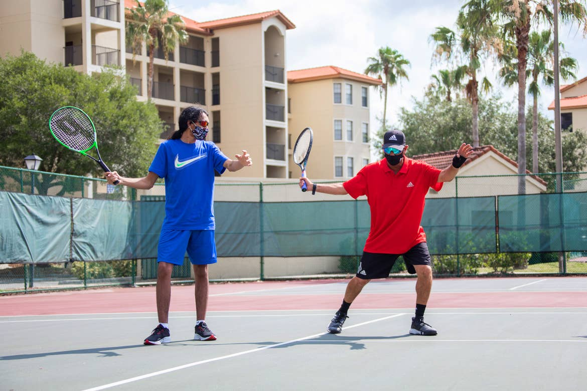 Special Olympic Athlete, Roan Luallen, plays tennis wearing a blue t-shirt and shorts with a safety mask and sunglasses with our instructor, Ernie, on the courts of our Orange Lake Resort located in Orlando, Florida.