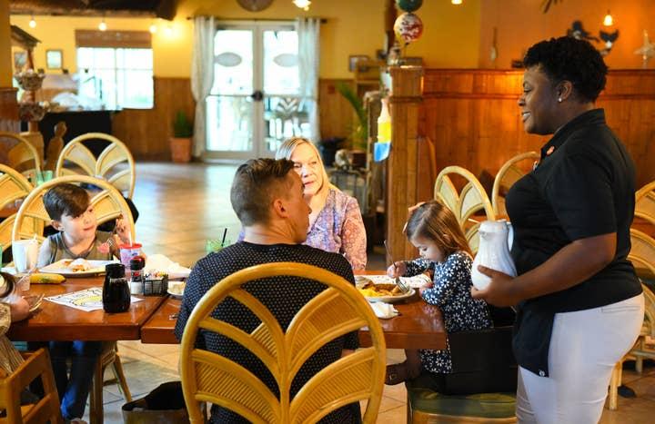 Family speaking to waitress at Orange Lake Resort near Orlando, Florida