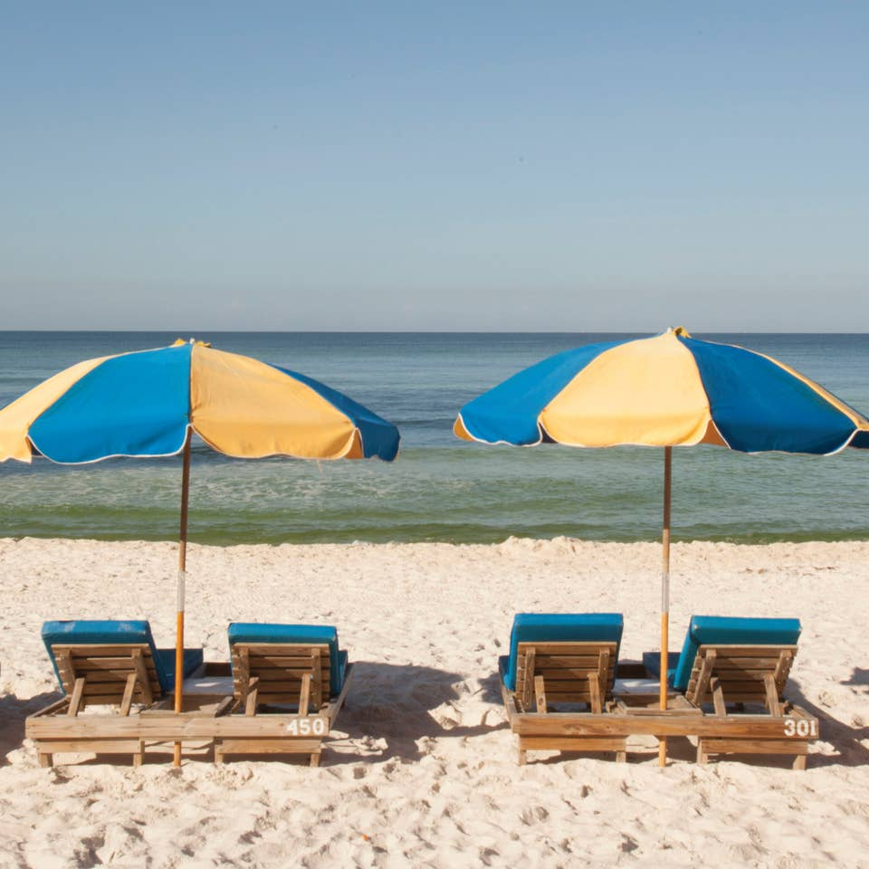 View of four beach chairs under two umbrellas at Panama City Beach in Florida.