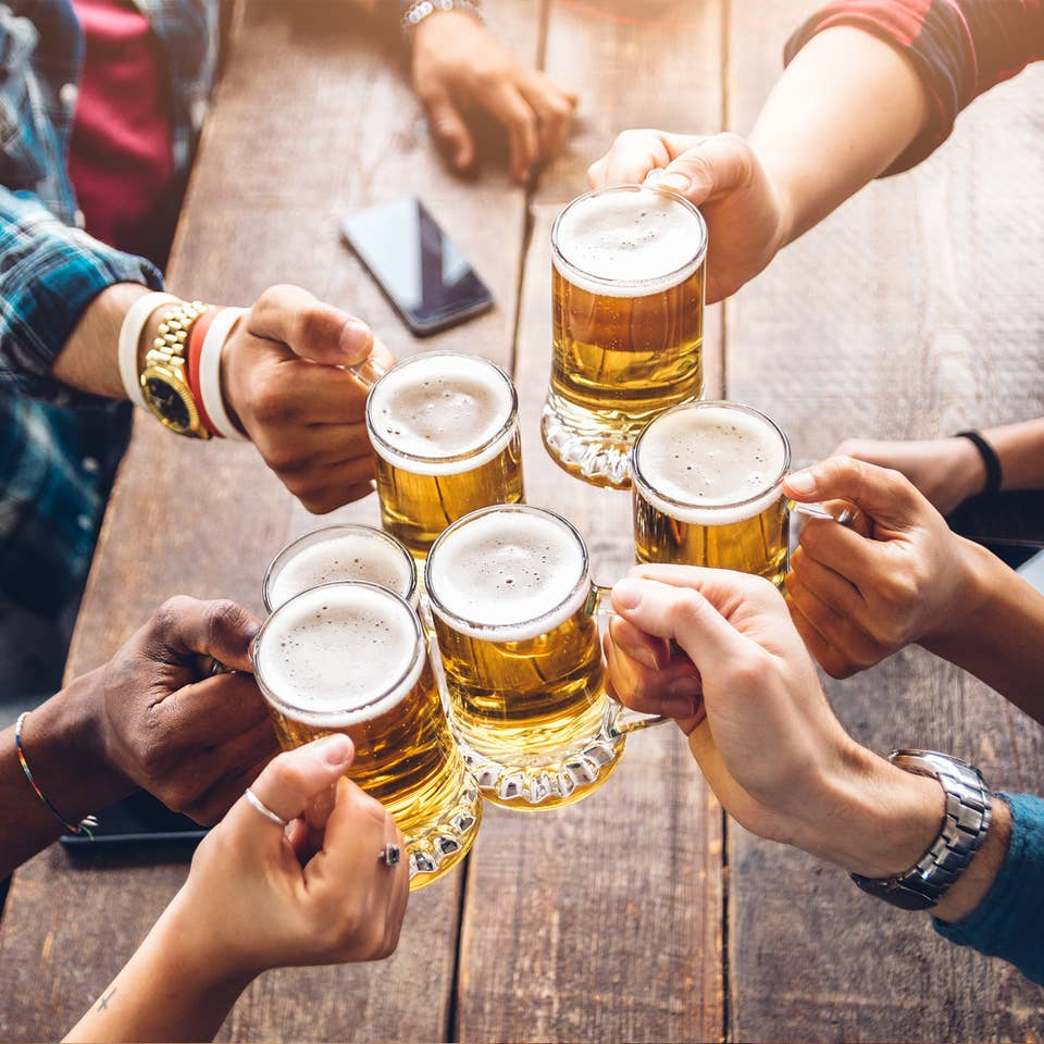 Several people hold their glasses of beer over a table giving 'cheers' to each other.