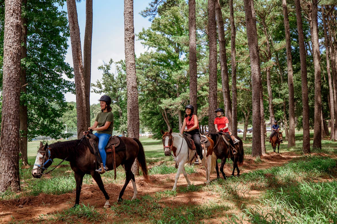 A tour guide on horseback leading four other riders near Apple Mountain Resort.