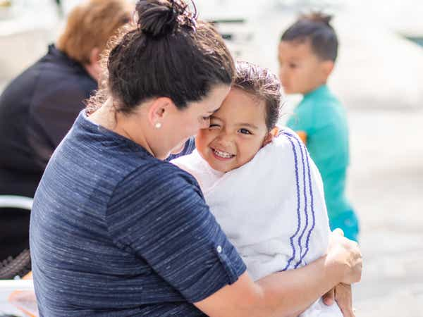 Adult hugging young child wrapped in towel by outdoor pool at Holiday Hills Resort in Branson, Missouri.