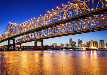 New Orleans bridge lit up at night.