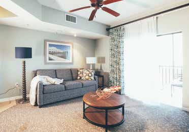 Living room with couch, access to balcony, and ceiling fan in a one bedroom villa in River Island at Orange Lake Resort near Orlando, Florida